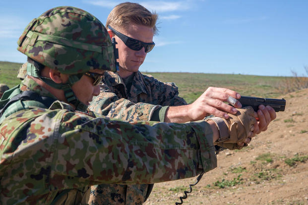 Marine Corps Sgt. Mason Wilhelmy assists a soldier of the Japan Ground Self-Defense Force's Western Army Infantry Regiment's Scout Sniper program with proper pistol grip during an abbreviated scout sniper course. (Photo: Lance Cpl. Timothy Valero)