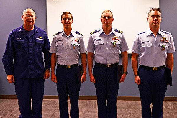 Rear Adm. Richard Gromlich, commander Coast Guard 13th District, stands with Lt. Justin Church, Lt. Wesley Jones and Petty Officer 1st Class James Froese, all three aviators at Coast Guard Air Station North Bend, Ore. (U.S. Coast Guard/PO1 Levi Read)