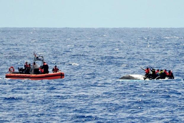 A small boat crew from the U.S. Coast Guard Cutter Bernard Webber approaches 10 people on top of an overturned vessel April 9, 2016. (Photo: U.S. Coast Guard)