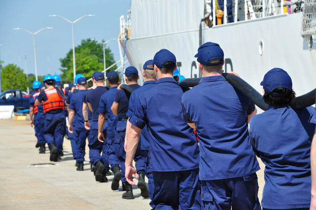 Coast Guard Cutter Tampa crew members carry a shore power cable on the pier at Base Portsmouth, Virginia, April 27, 2016. (Photo: Petty Officer 1st Class Melissa Leake)