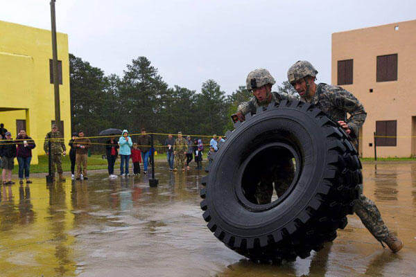 Army Staff Sgt. Erich Friedlein, left, and Army Capt. Robert Killian, move a large truck tire while competing in the 2016 Lt. Gen. David E. Grange Jr. Best Ranger Competition at Fort Benning. (Army National Guard/Staff Sgt. D. Richard Salzer)