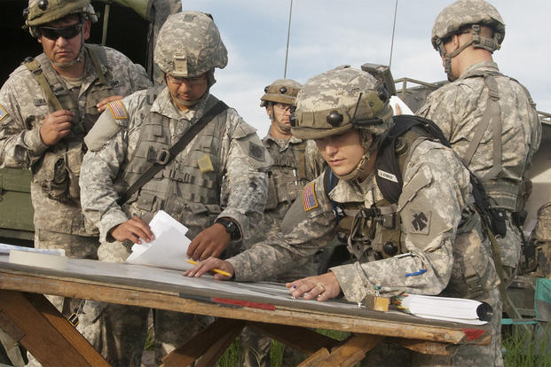 1st Lt. Kayla Christopher, fire direction officer, works with fellow officers to calculate distance and trajectories to targets while planning a fire mission for the battery during training at Fort Riley, Kansas. (U.S. Army/Sgt. Anthony Jones)