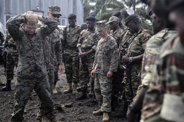 Lance Cpl. Christopher Parsons and Lance Cpl. Dustin Kitts show Cameroonian soldiers how to conduct personnel searches in Limbé, Cameroon, June 30, 2016. (Photo: Cpl. Alexander Mitchell)