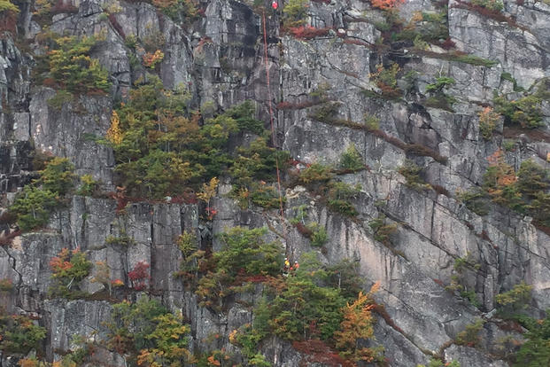 A helicopter crew from Coast Guard Air Station Cape Cod is on scene Saturday, October 8, 2016 to hoist a climber from a cliff in Acadia National Park in Maine. (U.S. Coast Guard photo)