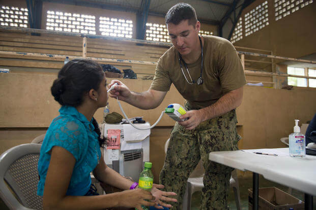 Hospital Corpsman 3rd Class Christopher Archuleta, attached to Naval Hospital Jacksonville, takes the temperature of a patient at the CP-17 medical site in Puerto Barrios, Guatemala. (U.S. Navy/Mass Communication Specialist 2nd Class Shamira Purifoy)