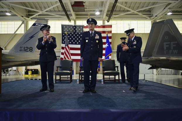 U.S. Air Force Chief of Staff Gen. David L. Goldfein and General Hawk Carlisle applaud for Gen. James M. Holmes during ACC's Change of Command ceremony at Joint Base Langley-Eustis, Va., March 10, 2017 (U.S. Air Force/Kimberly Nagle)