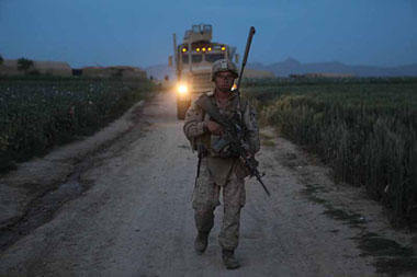 An infantryman with 3rd Battalion, 4th Marines, escorts a combat vehicle full of supplies for an observation post in Helmand province, Afghanistan. Cpl. Marco Mancha/Marine Corps