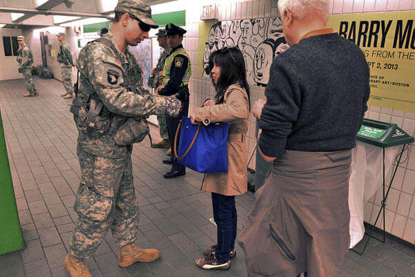 An Army National Guard member searches the bag of a woman as she entered an MBTA subway station near Boston Common, one day after a pair of bombs exploded at the finish line of the Boston Marathon.