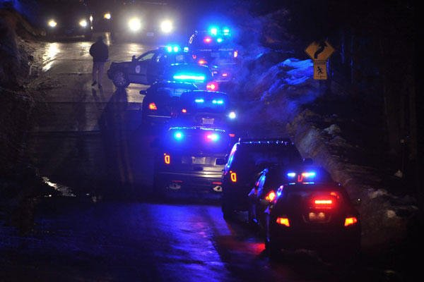 Police vehicles line a road leading to a Cape Cod condo community where one woman was shot to death and two other people, including a police officer, were wounded early Feb. 5 in Bourne, Mass. Steve Heaslip/Cape Cod Times via AP