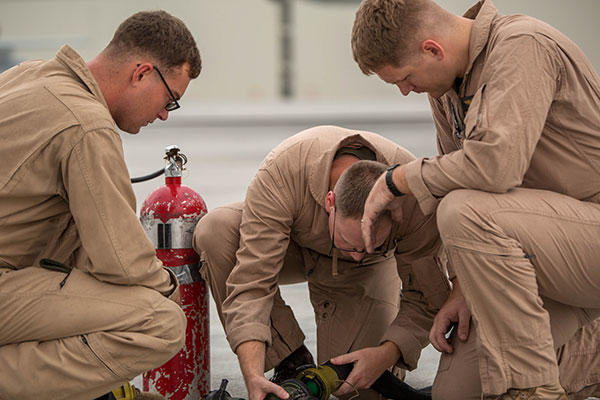Cpl. Mason Stone, Staff Sgt. David Hoyt, and Cpl. Greg Gambrell set up the refueling site for air delivery ground refueling training. (Cpl. Carlos Cruz Jr./U.S. Marine Corps)