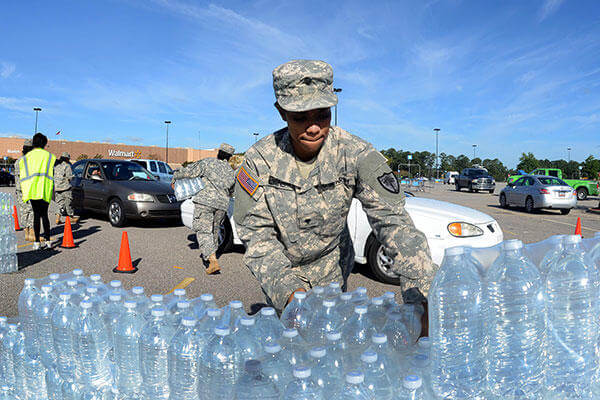 Army National Guardsmen distribute drinking water to residents affected by heavy rainfall caused by Hurricane Joaquin at the Lower Richland High School, Columbia, S.C., Oct. 6, 2015. (SC Air National Guard/A1C Ashleigh S. Pavelek)