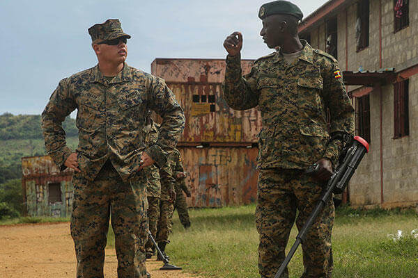 Sgt. Sean O'Hair, a combat engineer with Special-Purpose Marine Air-Ground Task Force Crisis Response-Africa, helps a member of the Uganda People's Defense Force through an IED awareness exercise. (U.S. Marine Corps/Cpl. Olivia McDonald)
