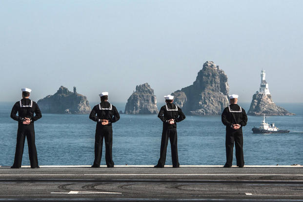 Sailors man the rails as the U.S. Navy's only forward-deployed aircraft carrier USS Ronald Reagan (CVN 76) departs Busan after a goodwill port visit. (Photo: Mass Communication Specialist 3rd Class Nathan Burke)