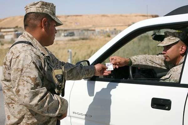 Marine checks ID at at Al Asad Air Base, Iraq. (Photo: Cpl. Daniel Redding, U.S. Marines)