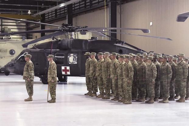 "Soldiers of Company C, 2nd General Support Aviation Battalion, 1st Aviation Regiment, 1st Combat Aviation Brigade, 1st Infantry Division, sing the ""Big Red One"" song during a deployment ceremony at Fort Riley July 13. (Sgt. Jarrett Allen)"