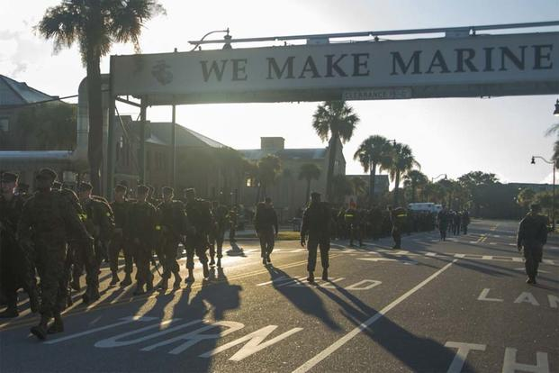 "Recruits hike under the iconic ""We Make Marines"" sign during the Crucible Aug. 26, 2016, on Parris Island, S.C. (Photo by Lance Cpl. Aaron Bolser)"
