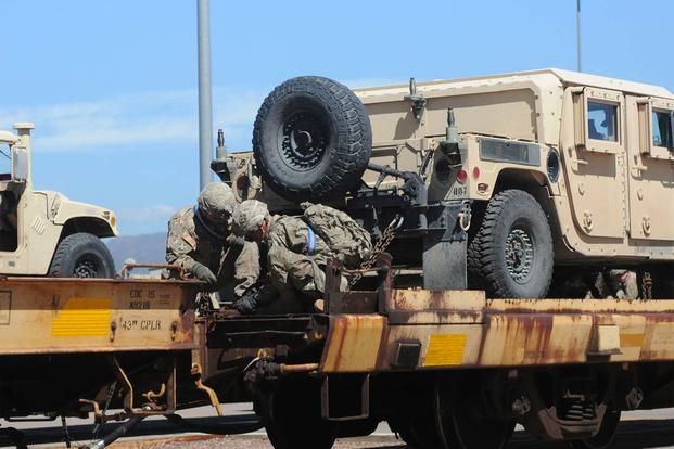 Soldiers from the 3rd Armored Brigade Combat Team, 4th Infantry Division secure a Humvee onto a rail car during the brigade's rail-load operations at the Fort Carson railhead, Aug. 9, 2016. (Army/Capt. Scott Walters.)