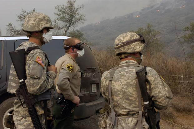 California National Guard Soldiers flank Deputy Todd Viller of the San Diego County Sheriff's Office as the three monitor progress of a wildfire near Valley Center, Calif. (Photo Credit: Staff Sgt. Jim Greenhill)