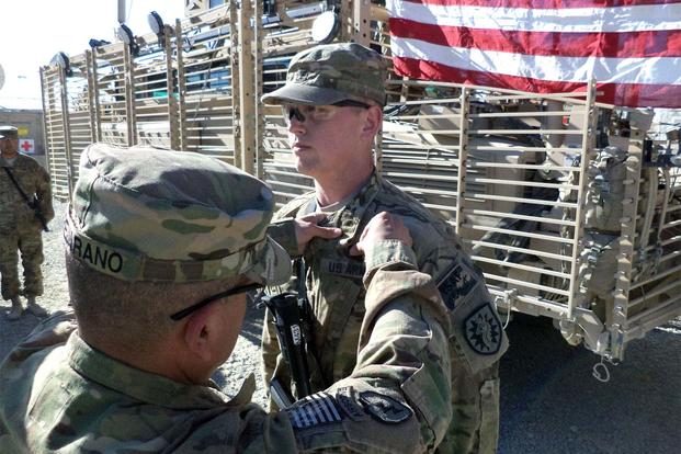 Cpl. Christopher Garland, a member of the California National Guard, receives the Army Commendation Medal for valor, and a Combat Medic Badge, at Forward Operating Base Ghazni. (Army Photo: 1st Lt. Antonia Elena Pearse)