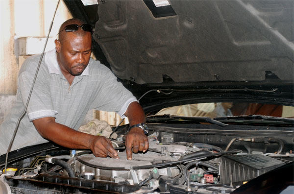 man looking under car hood