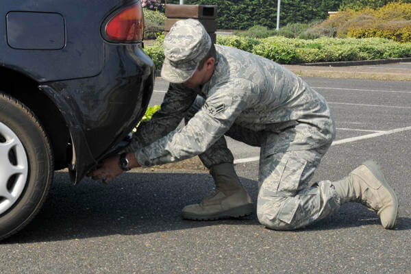 Servicemember near car's rear bumper.
