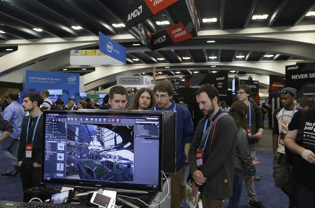 In this March 19, 2014 file photo, attendees to the Game Developers Conference 2014 look at screens in the Unreal Engine booth in San Francisco.