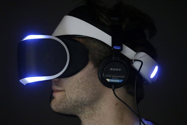 In this March 19, 2014 file photo, Marcus Ingvarsson tests out the PlayStation 4 virtual reality headset Project Morpheus in a demo area at the Game Developers Conference 2014 in San Francisco.