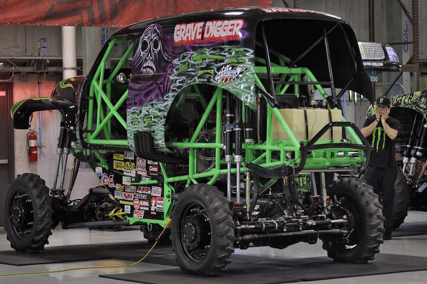 "Coty Saucier, far right, covers his ears as the Monster Truck ""Grave Digger"" gets it's engine started Tuesday, Nov. 25, 2014, at Feld Entertainment in Ellenton, Fla."