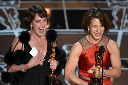 "Dana Perry, left, and Ellen Goosenberg Kent accept the award for best short subject documentary for ""Crisis Hotline: Veterans Press 1"" at the Oscars on Sunday, Feb. 22, 2015. (Photo by John Shearer/Invision/AP)"