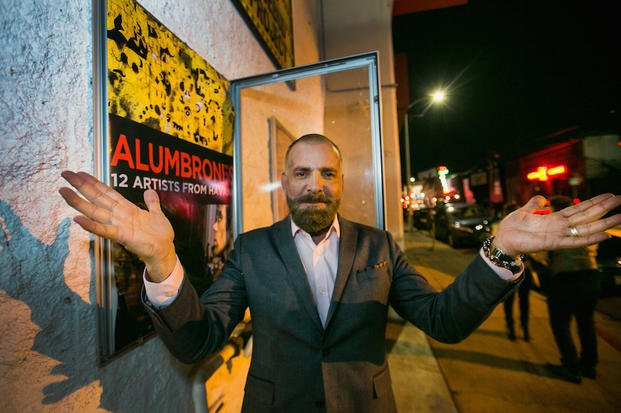 "In this Friday, Jan. 16, 2015 photo, Cuban producer Fermin Rojas poses with the poster of his film, ""Alumbrones,"" Spanish for illuminations, before its opening at the Arena Cinema Hollywood in Los Angeles."