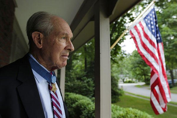 In this July 12, 2013, photo, retired U.S. Navy Capt. Thomas Hudner, who was awarded the Medal of Honor by President Truman, poses on the porch at his home in Concord, Mass.