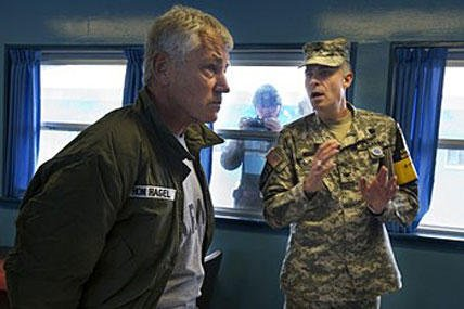 Defense Secretary Chuck Hagel, left, listens to U.S. Army Col. James Minnich, as a North Korean soldier, center, takes a photograph through a window at a UN truce village building that sits on the border of the Demilitarized Zone (DMZ).
