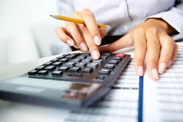 Businesswoman using a calculator and pencil.