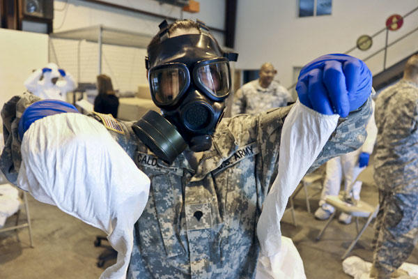 Army Spc. Kristal Calderon practices donning and removing protective equipment and a mask after a class at the logistical warehouse on Fort Gordon, Ga., Oct. 14, 2014. DoD photo