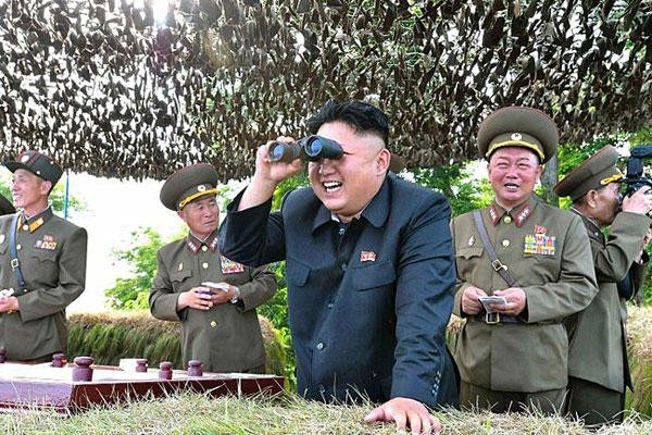 Kim Jong Un looks through a pair of binoculars during an inspection of the Hwa Islet Defense Detachment in this undated photo released by North Korea's Korean Central News Agency (KCNA) on July 1, 2014.