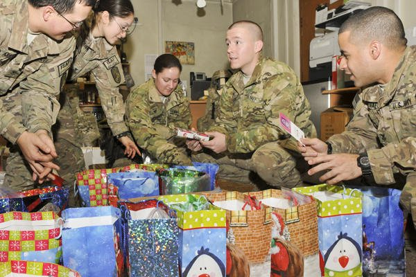 Service members gather around Christmas presents.