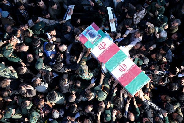 Iranian civilians and troops carry the flag-draped coffin of Brig. Gen. Hamid Taqavi, a senior Revolutionary Guard commander who was killed during a battle against the Islamic State extremist group in Iraq, on Monday, Dec. 29, 2014. Ebrahim Noroozi/AP