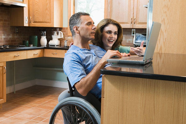 Veteran in wheelchair looking at laptop with wife