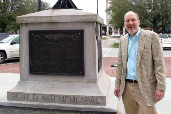 In this Jan. 22, 2015 photo, Greenwood Mayor Welborn Adams stands beside the Greenwood County memorial in Greenwood, S.C., that honors its citizens who died in recent wars. (AP Photo/Jeffrey Collins)