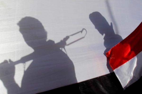 The shadow of Shiite rebels, known as Houthis, are cast on a large representation of the Yemeni flag as they attend a demonstration against an arms embargo in Sanaa, Yemen, April 16, 2015. (AP Photo/Hani Mohammed)