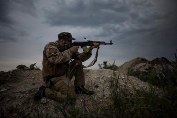 In this photo taken Tuesday, June 23, 2015, a Ukrainian serviceman from the Kiev-2 volunteer battalion fires his gun at a frontline in the village of Krymske, east Ukraine. (Evgeniy Maloletka/AP Photo)