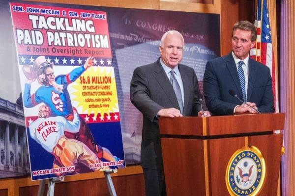 Sens. John McCain and Jeff Flake of Arizona during a press event on Capitol Hill on Wednesday, Nov. 4, 2015, stand beside a billboard touting the results of a report questioning a Pentagon program that doles out millions of dollars to professional sports
