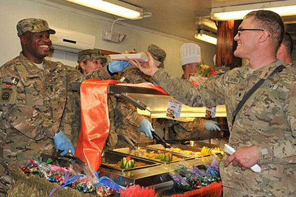 Command Sgt. Maj. Christopher T. Crawford gives Spc. Victor W. Stephans his food while serving lunch at the Koele Dining Facility on Thanksgiving Day, Nov. 28, 2013, at Bagram Air Field, Afghanistan. Sgt. Sinthia Rosario/Army