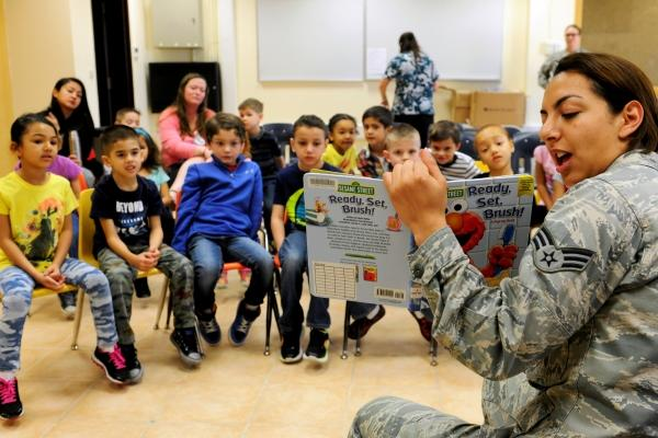 Senior Airman Ana Gomez-Martinez, 39th Medical Operations Squadron oral preventative technician, reads a book about dental health to children at Incirlik Unit School Feb. 19, 2016, at Incirlik Air Base, Turkey. (Photo by Jack Sanders/U.S. Air Force)