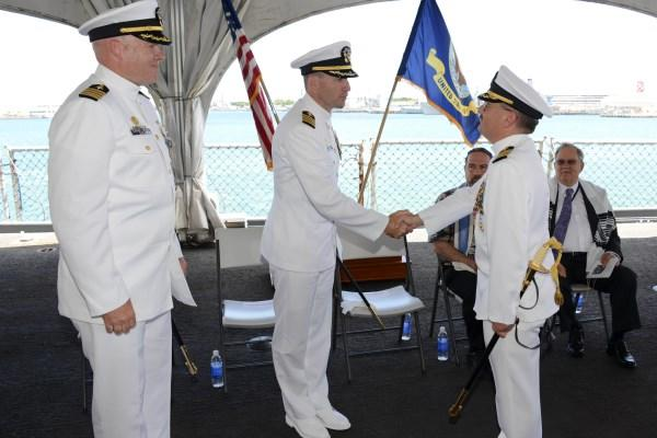 Capt. Howard Goldman, right, is congratulated by the commanding officer of the Submarine Learning Center as he relinquishes command of Naval Submarine Training Center Pacific during an Aug. 15, 2014, change of command ceremony. (Photo by Jason Swink/Navy)