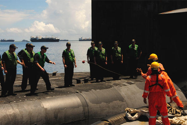 Crewmembers of the guided-missile submarine USS Florida (SSGN 728) handle a mooring line from a tug boat to be brought alongside submarine tender USS Emory S. Land (AS 39) in Diego Garcia. (US Navy/Zachary Kreitzer)