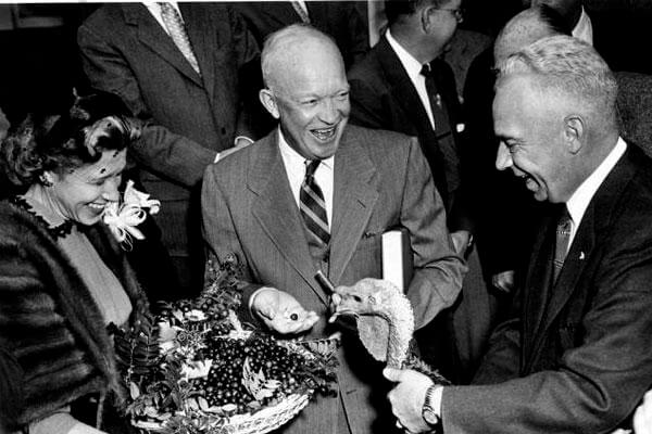 "November 14, 1954: President Dwight D. ""Ike"" Eisenhower receives a turkey from the president of the National Turkey Federation. Ike liked to have a bourbon ""punch"" in his holiday eggnog. (Eisenhower Presidential Library photo)"