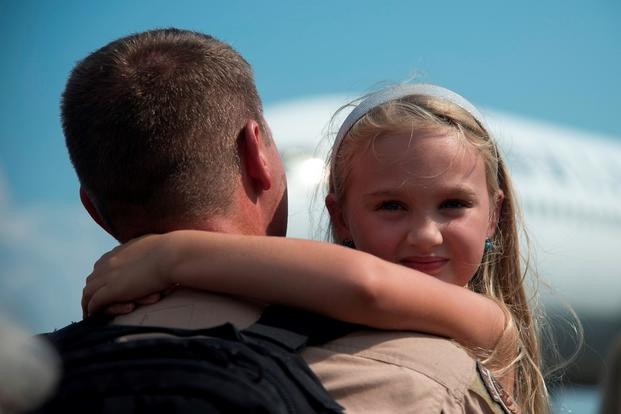 A girl smiles as she hugs her father during the return of the 17th Airlift Squadron on Sept. 4, 2013, at Joint Base Charleston Air Base, S.C. (U.S. Air Force photo/Rasheen Douglas)