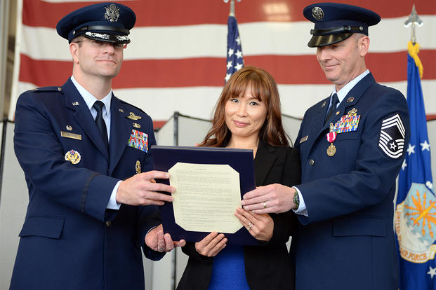 Mrs. Hyun Crites, wife of Chief Master Sgt. James Crites, 9th Operations Group superintendent (right), is presented the Military Spouse Medal during her husband's retirement ceremony. (Photo: U.S. Air Force photo /Senior Airman Bobby Cummings.)