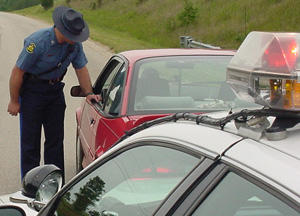 A highway patrol officer stops a red car.